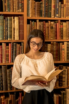 Young woman in glasses reading book near shelf