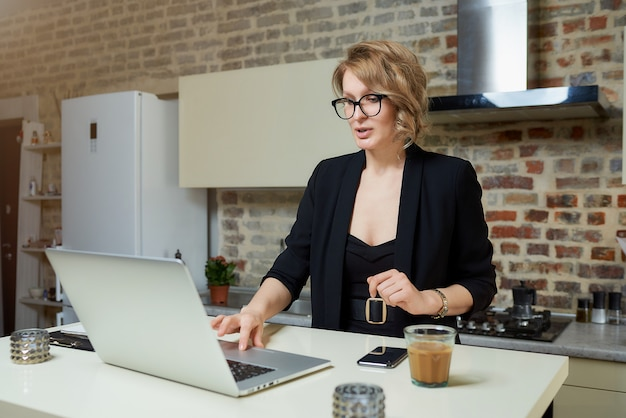 A young woman in glasses works remotely on a laptop in her kitchen. a serious girl browsing news on the internet at home. .