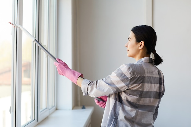 Young woman in gloves cleaning the window with mop at the office