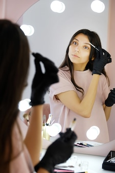 A young woman in gloves combs her eyebrows in a beauty salon, paints them with a brush before makeup.