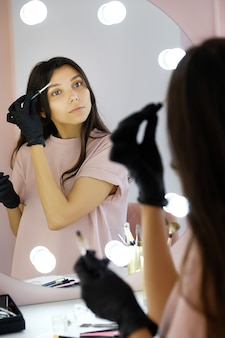 A young woman in gloves combs her eyebrows in a beauty salon