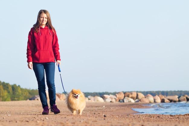 Молодая женщина идет со своей собакой на пляже.