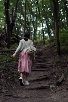 Young woman goes on a forest path. the girl herself walks in the woods. wild park. back view