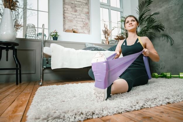 Молодая женщина занимается спортом дома, тренируется онлайн
