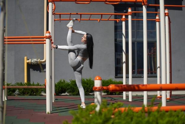 젊은 여자는 똑바로 세운 자세로 넓은 다리를 펴고 현대적인 놀이터에서 스포츠를 시작합니다.