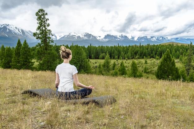 젊은 여자는 매트에 앉아 산에서 자연에서 요가를 연습하는 스포츠에 들어갑니다.