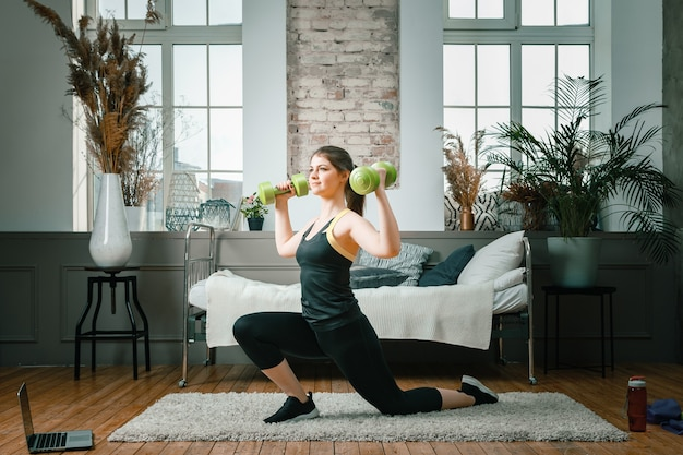 A young woman goes in for sports at home, online workout from the laptop