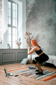 Young woman goes in for sports at home, training online. the athlete makes squat   with sport fitness rubber bands    on background bed, vase, carpet