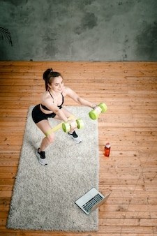Young woman goes in for sports at home, training online