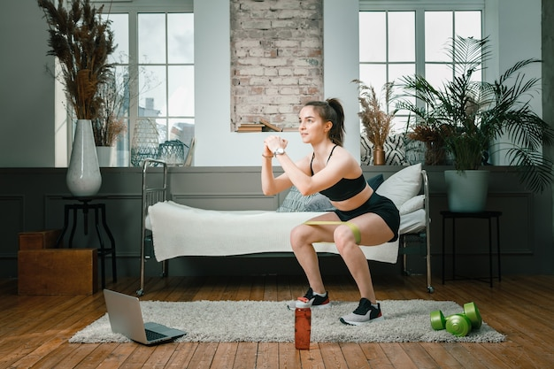 The young woman goes in for sports at home