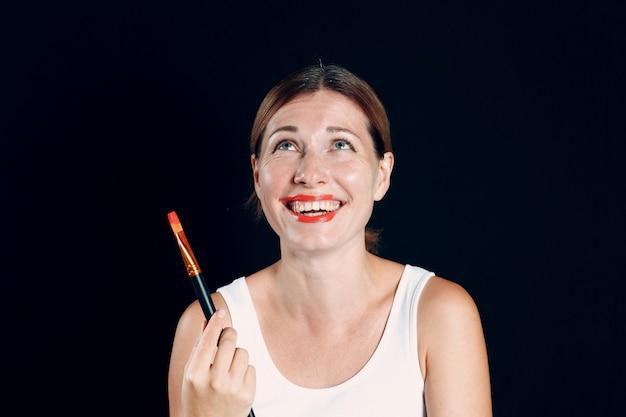 Молодая женщина собирается нанести макияж, рисует лицо кистью и макияж. как не сделать макияж концепции.