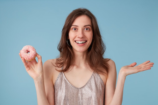 甘いピンクのドーナツを食べようとしている若い女性は、孤立した青い壁の上に、それを手に持っています