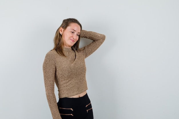 Giovane donna in maglione dorato e pantaloni neri che tengono la mano sulla testa e che sembra felice