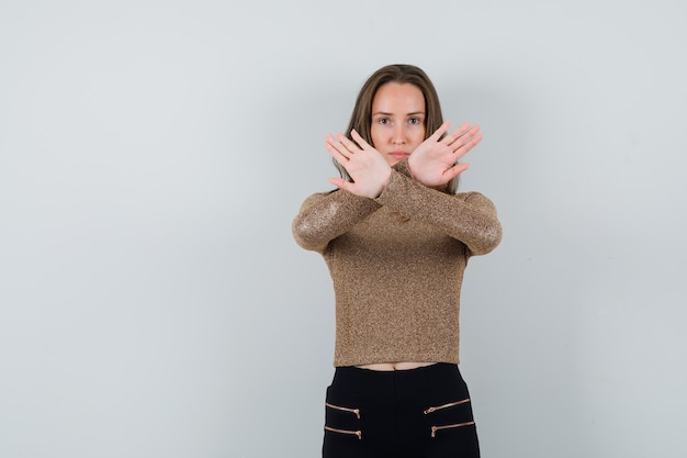 Giovane donna in maglione dorato e pantaloni neri tiene le braccia incrociate per fermare qualcosa e sembra seria