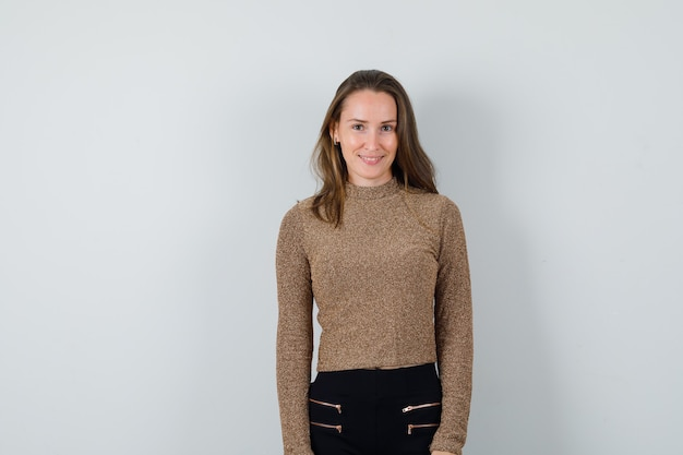Young woman in gold gilded sweater and black pants standing straight and smiling and looking happy
