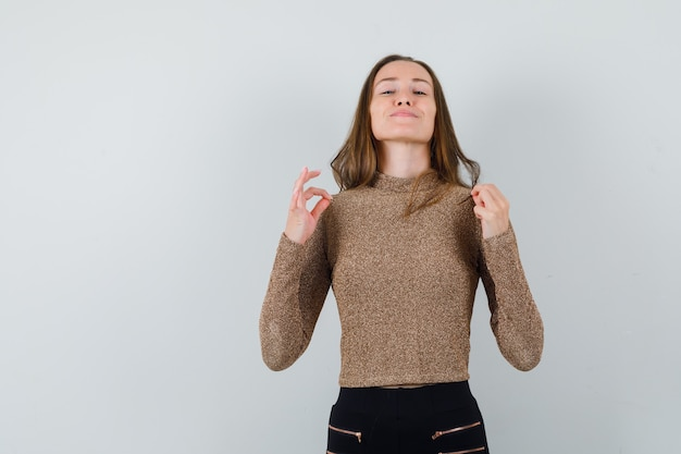 Young woman in golden blouse pinching her blouse and looking self-confident