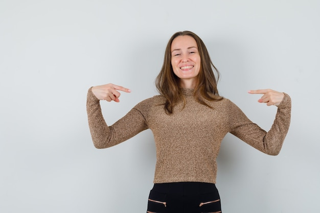 Young woman in golden blouse pointing at herself and looking glad