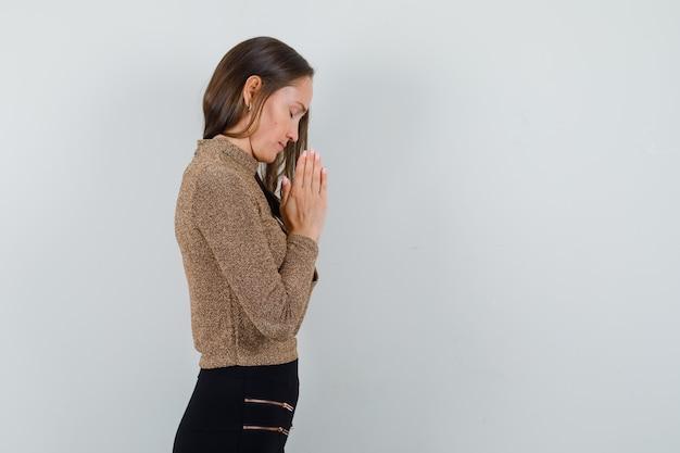 Giovane donna in camicetta dorata che prega e che sembra speranzosa. spazio libero per il testo