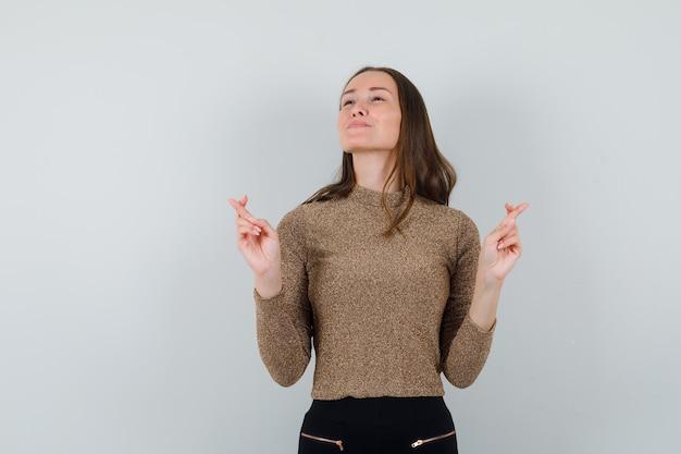 Giovane donna in camicetta dorata che mostra le sue dita incrociate mentre guarda lontano e sembra sicura