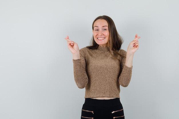 Giovane donna in camicetta dorata che mostra le sue dita incrociate mentre sorride e sembra allegra