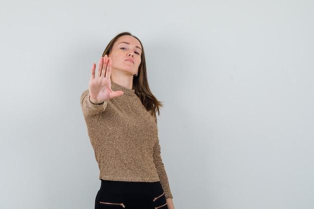 Giovane donna in camicetta dorata che mostra il gesto di arresto e che sembra rigorosa