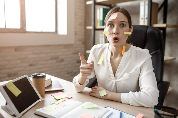 Молодая женщина получила идею. она сидит в комнате за столом, задается вопросом. модель ориентирована. ее лицо и стол, полный наклеек.