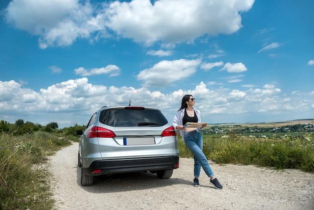 젊은 여성이 길을 잃고 새로운 여행을 계획하기 위해 지도를 찾고 있습니다. 차 근처 도로에 서 있는 여자