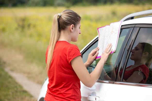 젊은 여자는 들판에서 길을 잃고 지도를 읽고 있다