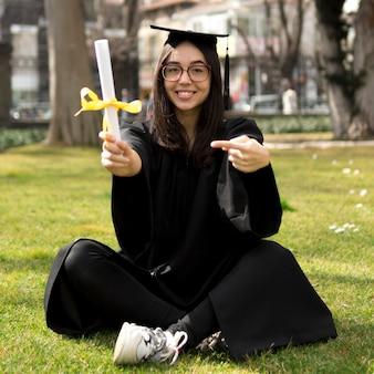 Giovane donna alla cerimonia di laurea fuori