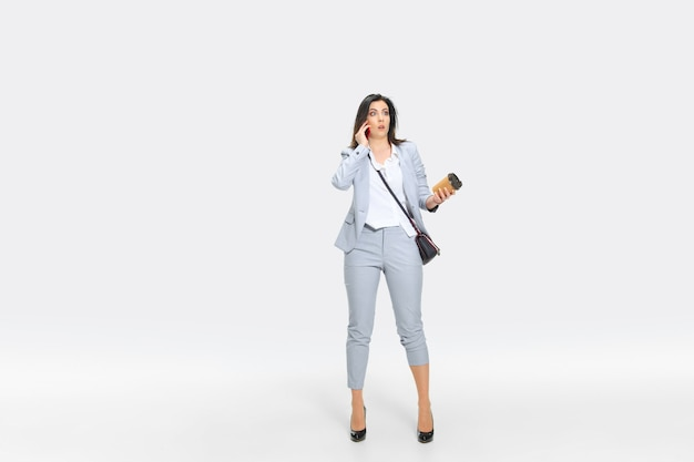 Young woman in gray suit is getting shocking news from boss or colleagues. looking numbed while dropping coffee. concept of office worker's troubles, business, stress.