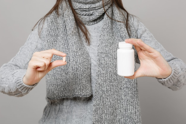 Young woman in gray sweater, scarf holding medication tablets aspirin pills in bottle isolated on grey background. healthy lifestyle ill sick disease treatment cold season concept. mock up copy space.