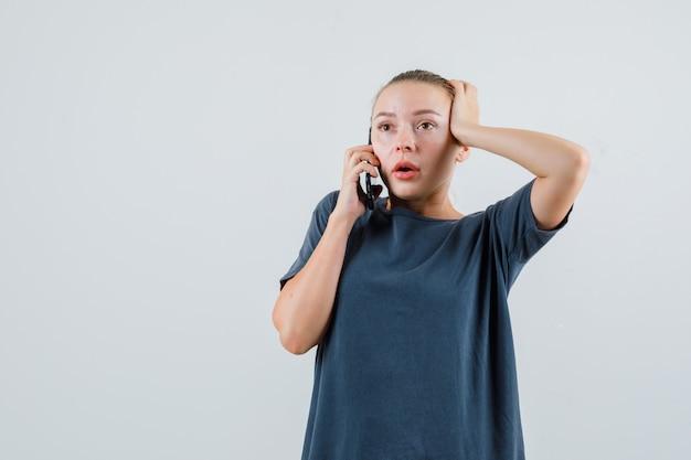 Giovane donna in maglietta grigia parlando al cellulare e guardando scioccata
