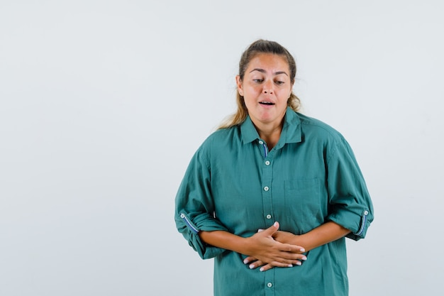 Young woman in green blouse having bellyache and looking exhausted
