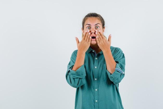 Giovane donna in camicetta verde tenendosi per mano vicino alla bocca e guardando sorpreso