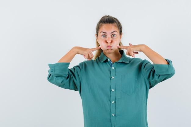 Giovane donna in camicetta verde sbuffando guance e indicando con le dita indice e guardando sorpreso
