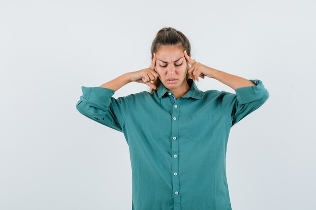 Young woman in green blouse rubbing temples and looking serious