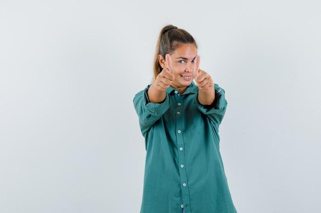 Giovane donna in camicetta verde che mostra i pollici in su con entrambe le mani e che sembra carina