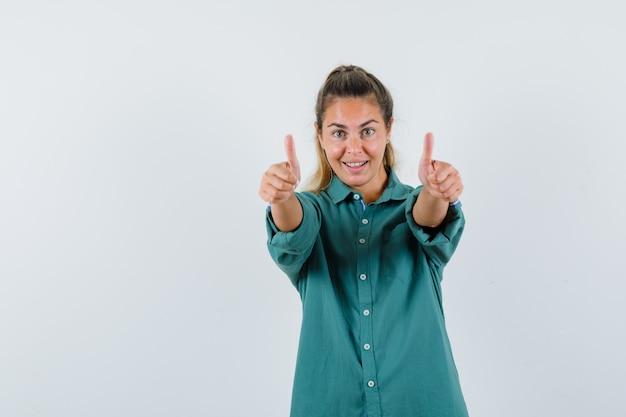 Giovane donna in camicetta verde che mostra i pollici in su con entrambe le mani e che sembra felice