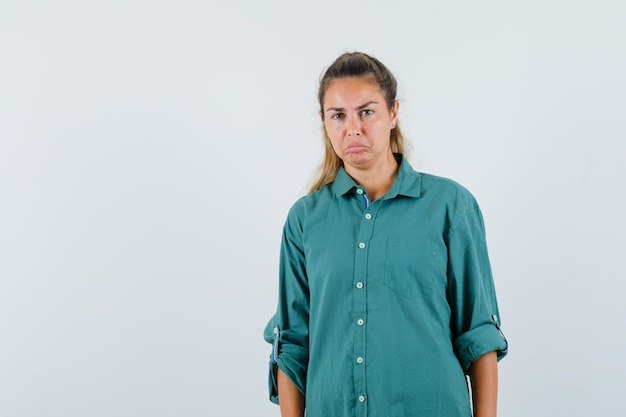 Young woman in green blouse standing straight and posing at front and looking displeased