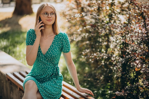 Young woman in green dress sitting in park