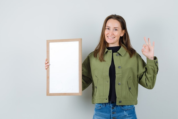 Young woman in green jacket holding blank frame while showing ok gesture and looking positive , front view.