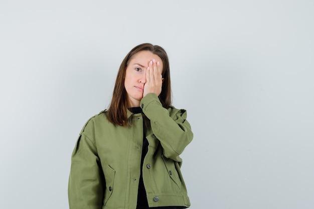 Giovane donna in giacca verde tenendo la mano sul viso e guardando nascosto, vista frontale.