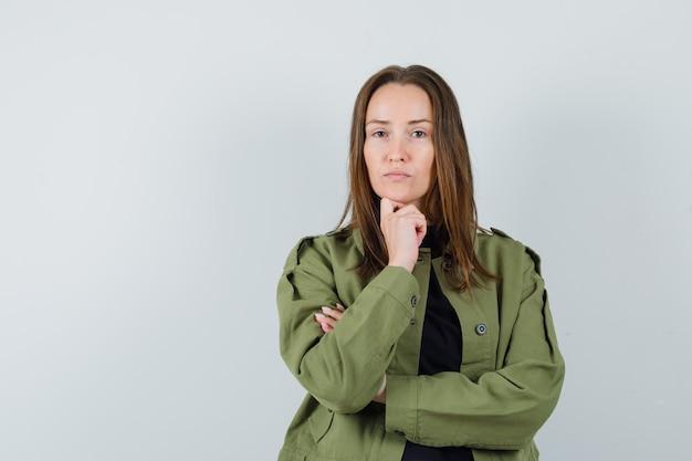 Giovane donna in giacca verde ascoltando qualcuno e guardando attento, vista frontale.