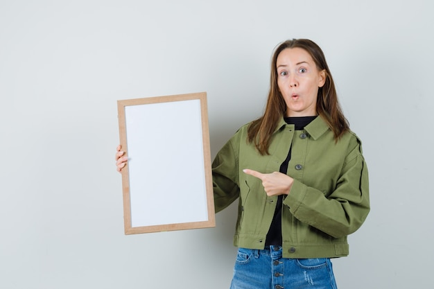 Young woman in green jacket pointing at blank frame and looking surprised , front view.
