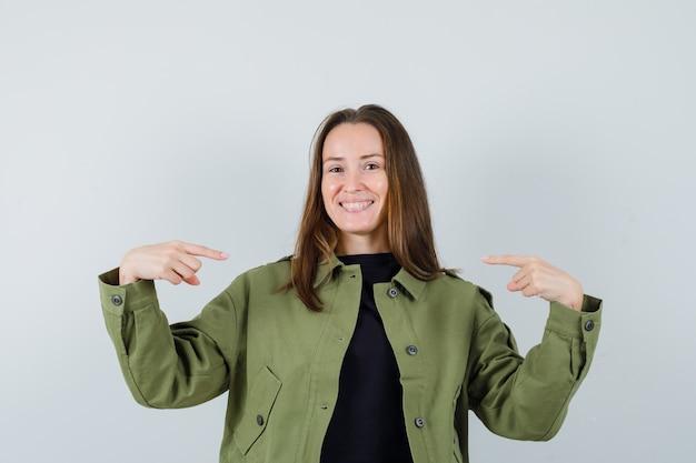 Giovane donna in giacca verde che punta a se stessa e guardando fiducioso, vista frontale.