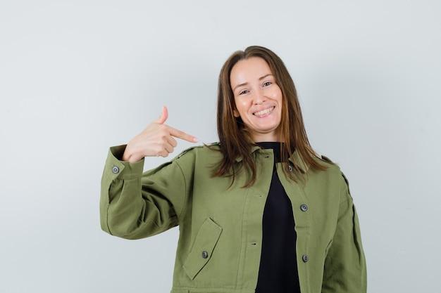 Giovane donna in giacca verde che punta a se stessa e che sembra felice, vista frontale.