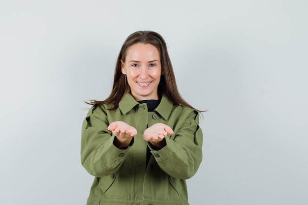 Young woman in green jacket posing like sharing something with someone and looking pleased , front view.