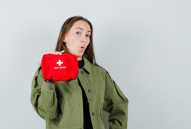 Giovane donna in giacca verde che mostra kit di pronto soccorso, vista frontale.