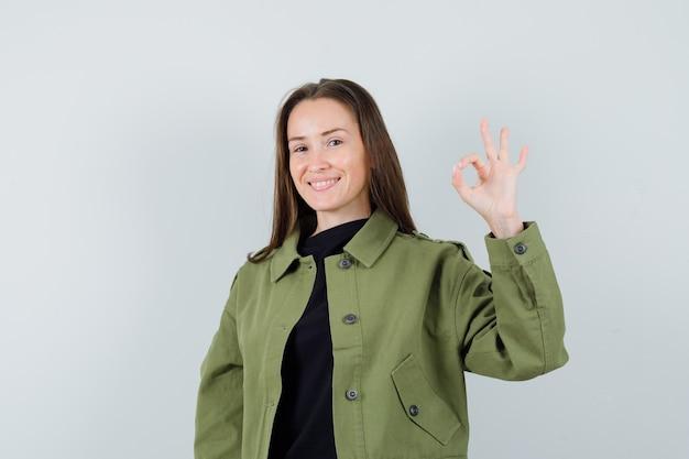 Giovane donna in giacca verde che mostra il gesto giusto e guardando ottimista, vista frontale.