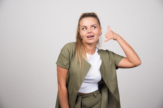 Giovane donna in camicia verde che chiama qualcuno.